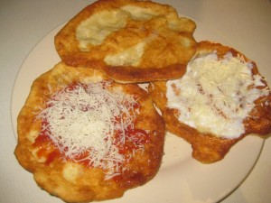 langosh topped with ketchup, sour cream, cheese and garlic