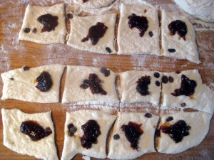dough cut into squares with plum jam filling