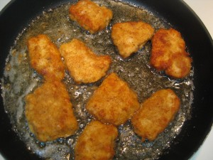 wiener schnitzels frying in oil