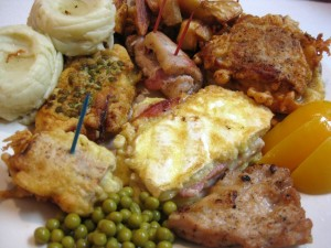 huge plate of cheese ham and egg loaded schnitzels with baked and mashed potoates apricots and peas