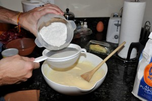 adding flour to egg mixture through a strainer